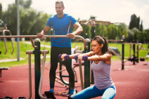 Young sporty woman exercising with dumbbells at the outdoor gym while young man is working out using exercise machine.